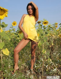 Adorable petite cutie strips off her cute yellow dress and poses naked among sun flowers.